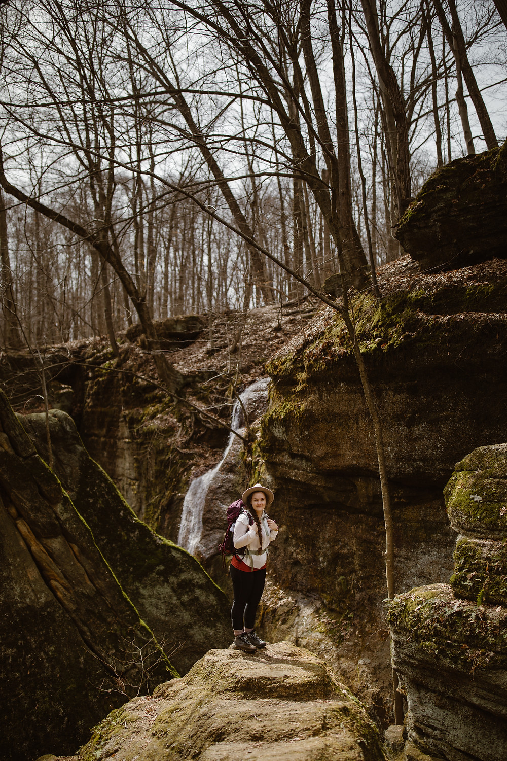 Ohio elopement photographer standing in front of a waterfall surrounded by moss covered ledges and trees