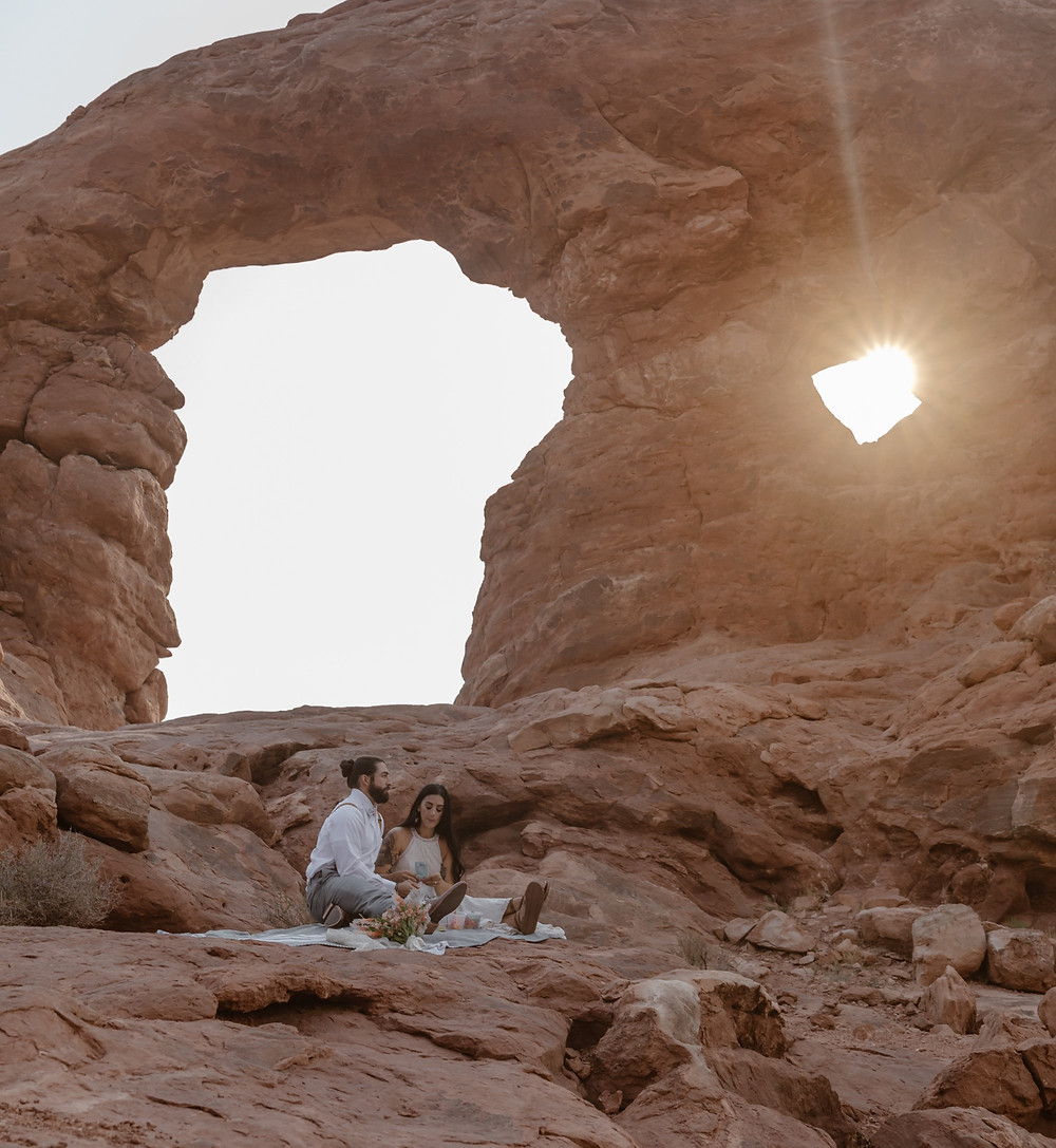 couple having a picnic under the turret arch at arches national park