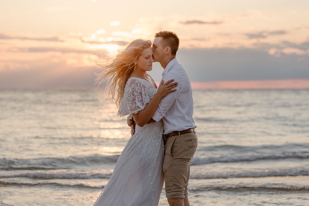 couple enjoying their first dance during sunset on a beach on their wedding day