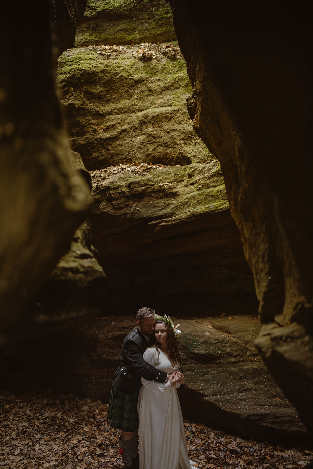 groom in Scottish kilt hugging wife from behind surrounded by moss covered ledges on their Nelson Kennedy Ledges Ohio elopement day