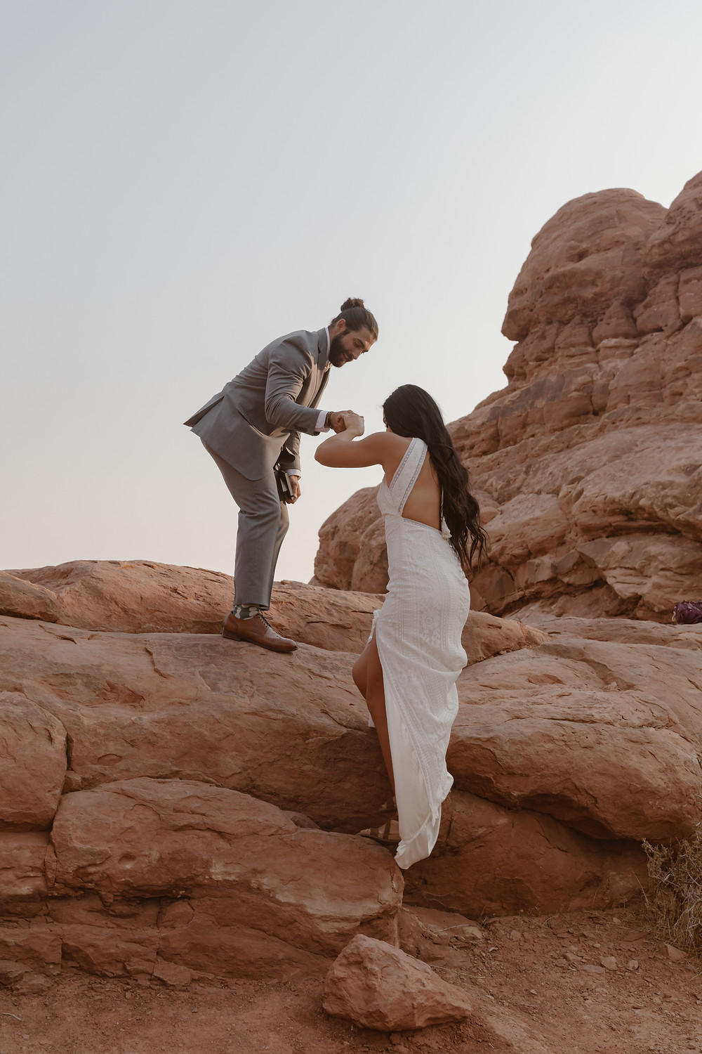 groom helping bride over some red rocks in arches national park