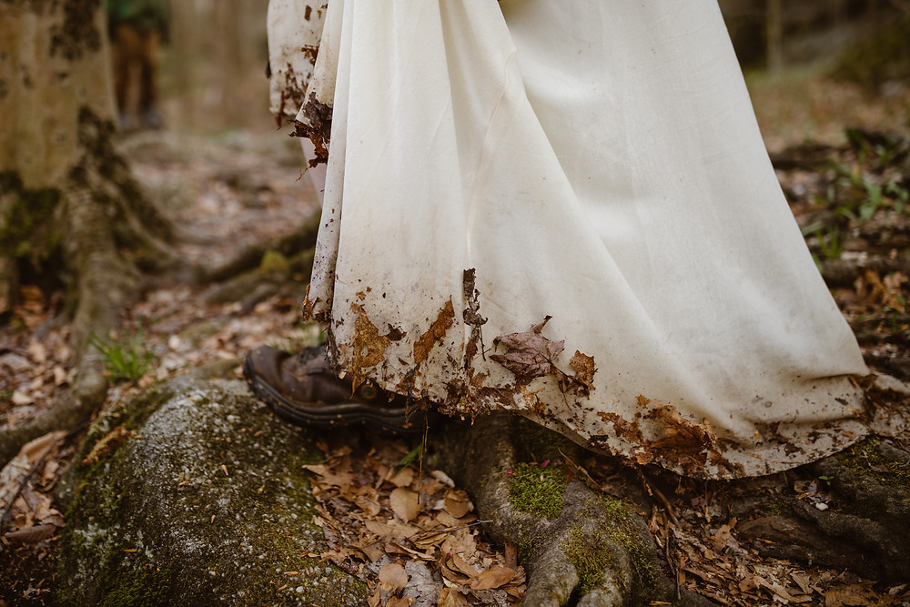 bride wearing hiking boots and a dress covered in fallen leaves and dirt walking over tree branches on her Ohio elopement