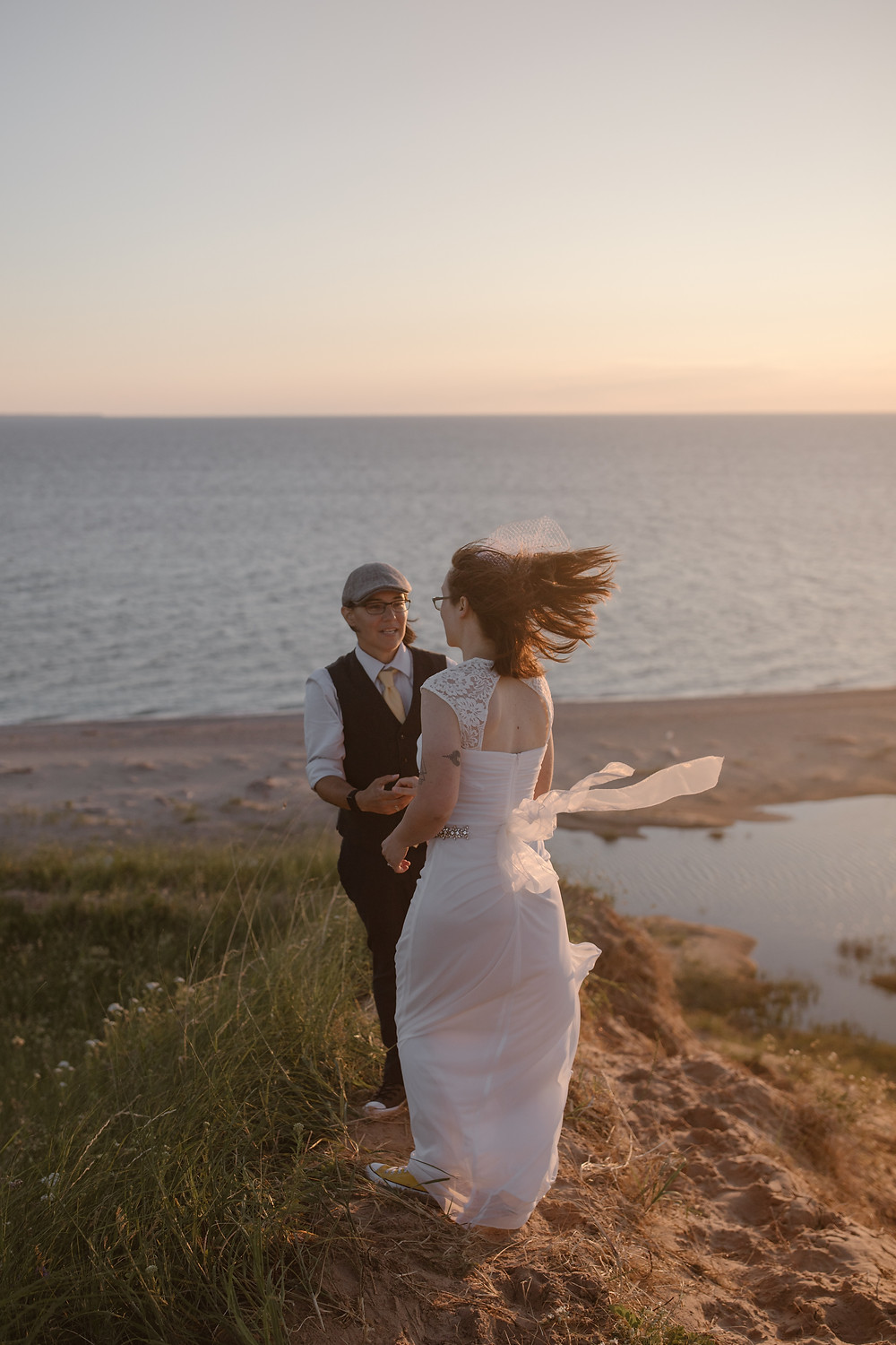 Couple windswept on a sand dune in Michigan on their elopement day