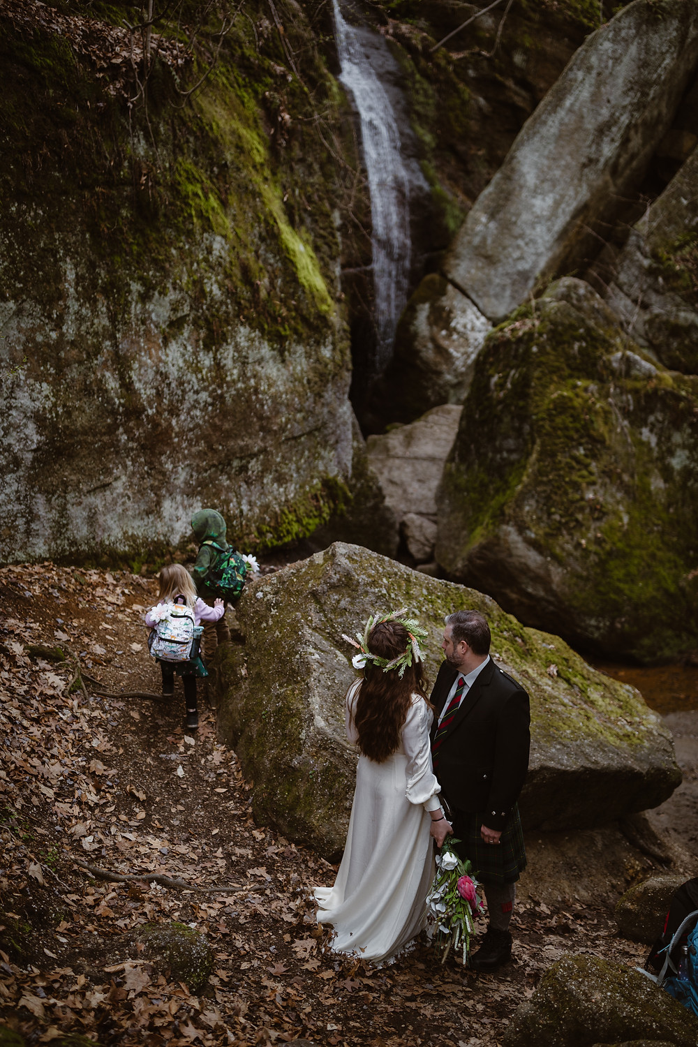 Bride and groom watching their kids play on their Nelson Kennedy Ledges Ohio elopement while standing in front of a rushing waterfall surrounded by large ledges covered in moss and fern