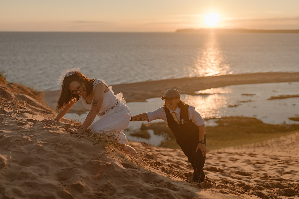 LGBTQ couple climbing a sand dune on their elopement in Michigan