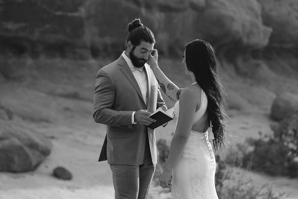 bride wiping grooms tear while reading vows on their elopement in arches national park