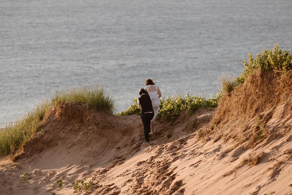 eloping couple walking on sand dunes overlooking Lake Michigan on their Michigan elopement day