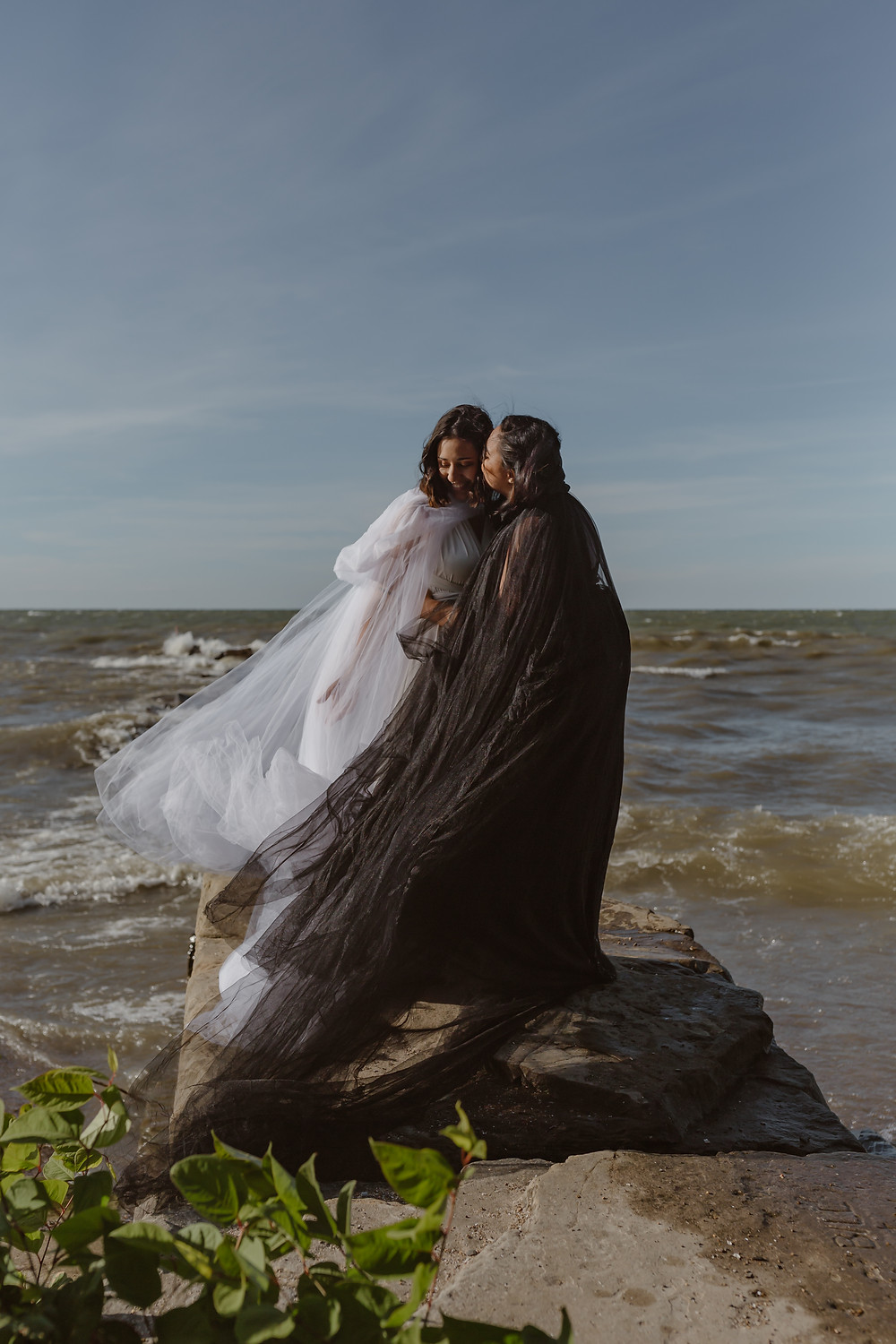 Cleveland Ohio elopement on Lake Erie a lesbian couple in a black wedding dress and a white wedding dress windswept and kissing