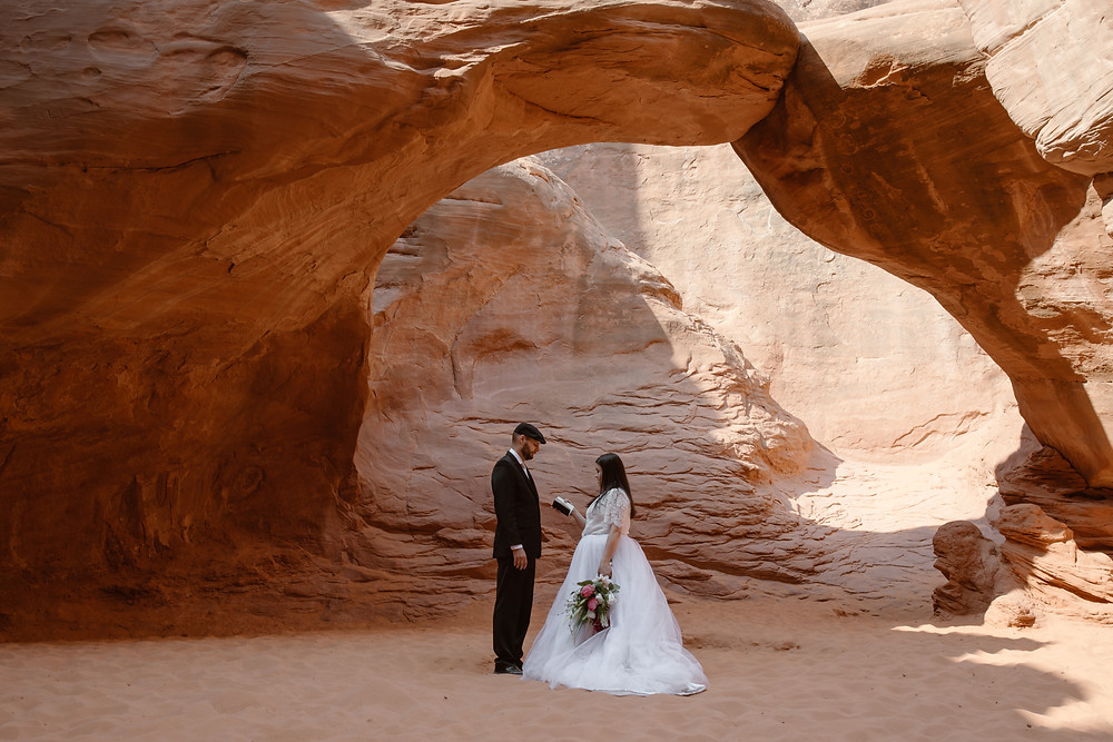 bride and groom reading their vows at the sand dune arch in arches national park