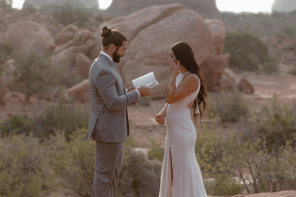 bride and groom reading vows and crying
