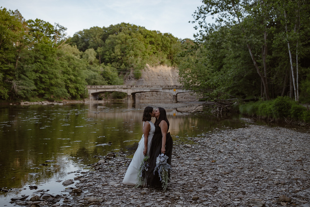 Lesbian couple kissing on their elopement day surrounded by trees and with a bridge and river in the background.
