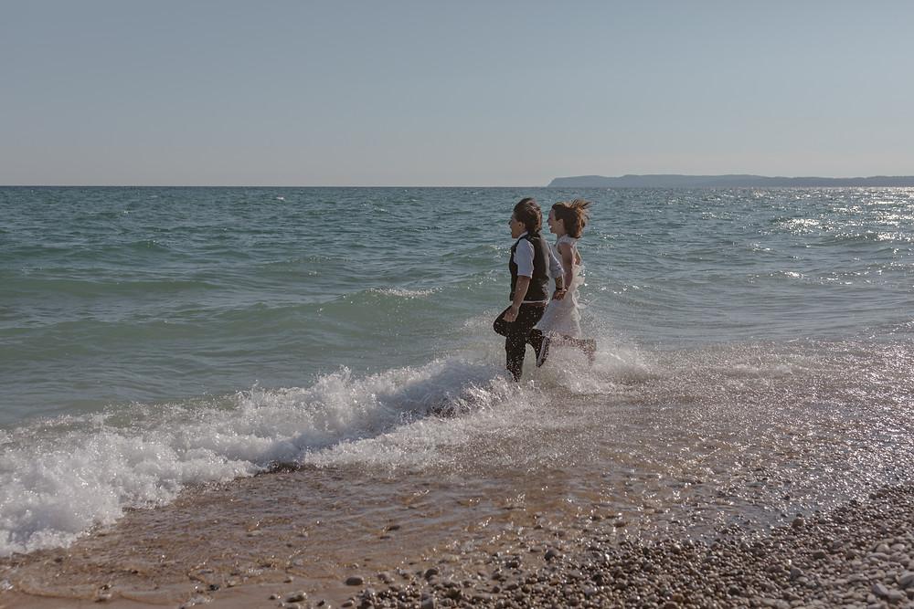 lesbian couple running into the ocean in their wedding attire on their wedding day