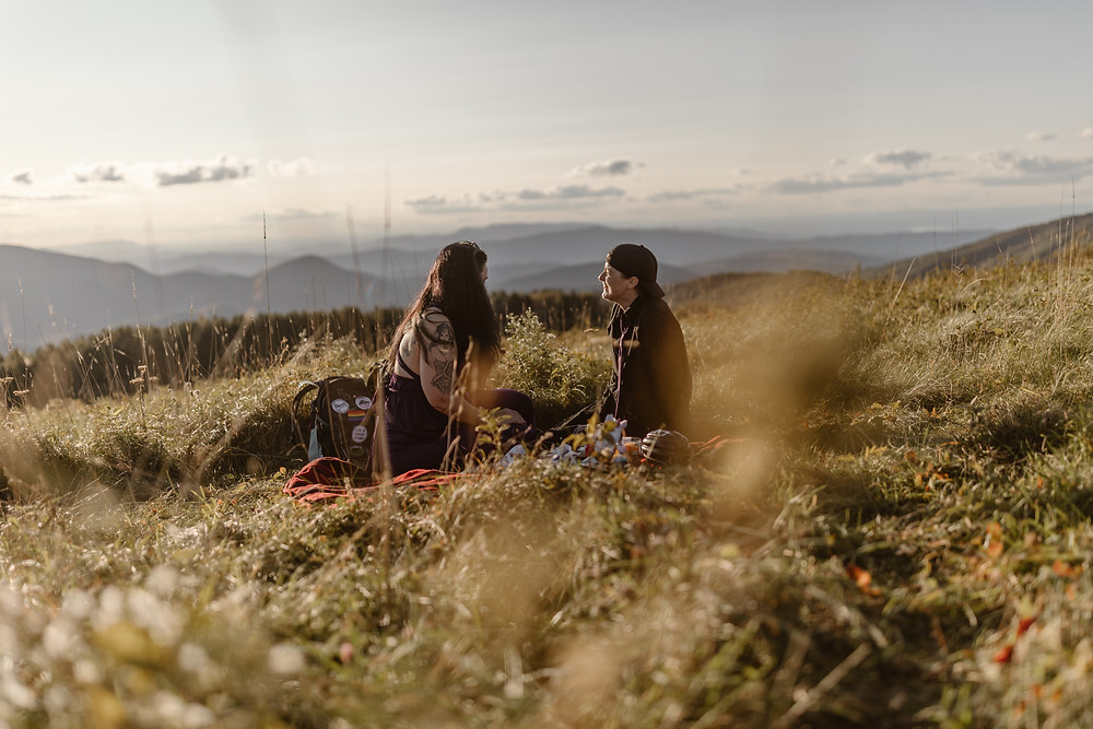 couple having a picnic on a mountain top on their elopement day