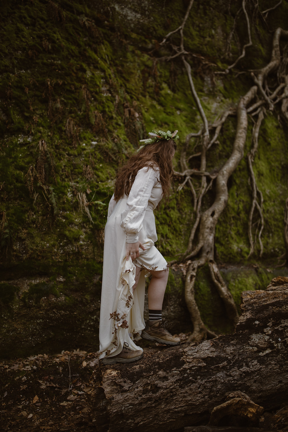 bride hiking walking on a log in her wedding dress that has leaves sticking at the bottom with large tree roots on a cliff behind her