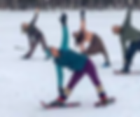 A yoga class doing traingle pose in the snow with snowshoes and winter clothes on.