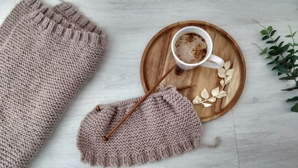 A coffee next to knitting supplies