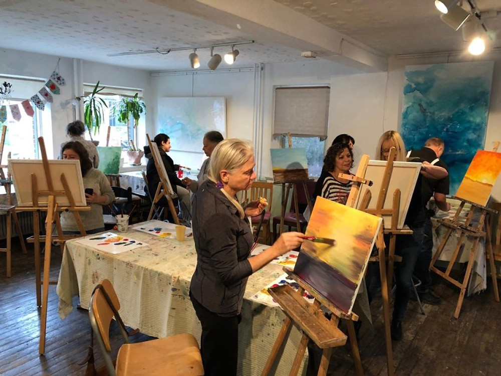 An older adult painting at a workshop in Toronto