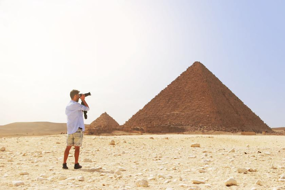 A guy taking a photo of the pyramids in Egypt