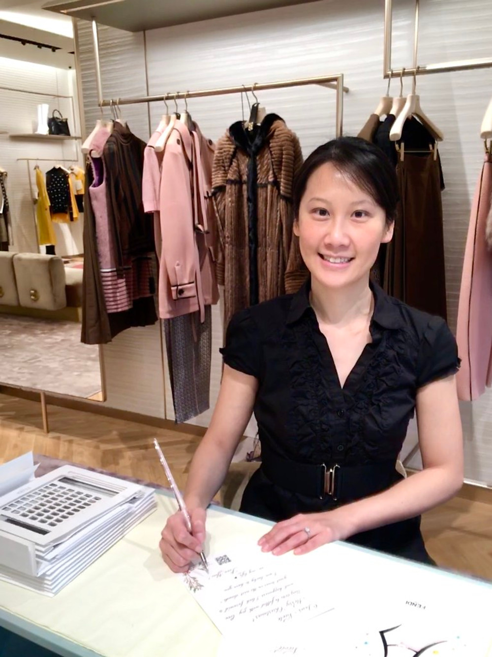 A picture of Claudia Chan showing her calligraphy skills