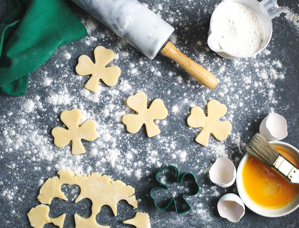 shamrock shaped cookies with flour, butter, rolling pin on counter