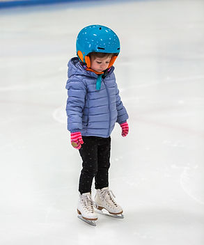 Toddler girl learning how to ice skate o