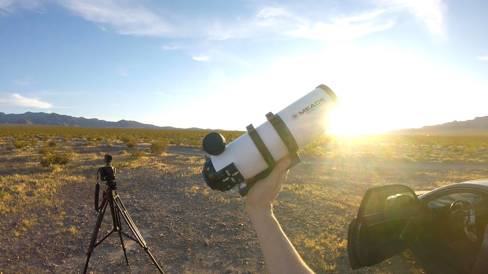 Holding a small telescope in the air at sunset