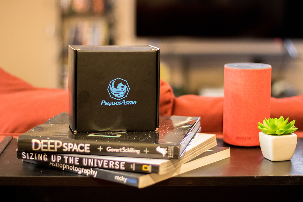 The box that contains the Pegasus Astro Pocket Powerbox, on top of astronomy and astrophotography books and next to Amazon Echo Alexa for size