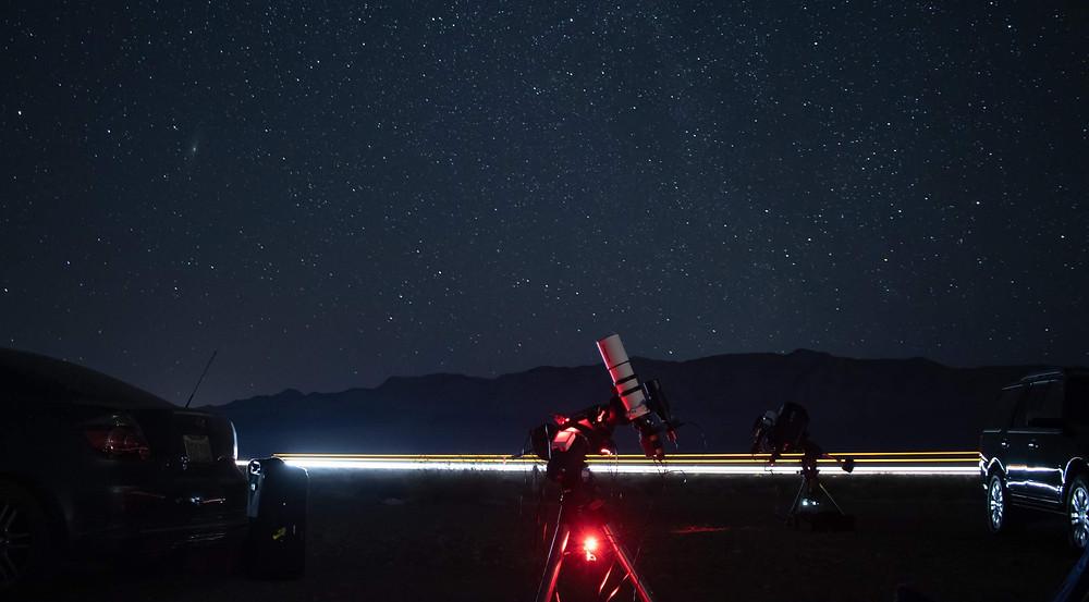Refractor telescope in the desert with light streak from cars
