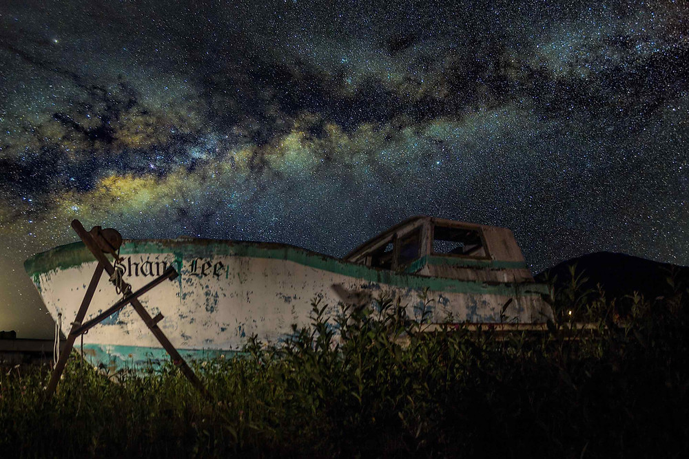 The Milky Way with a boat in the foreground from Alaska