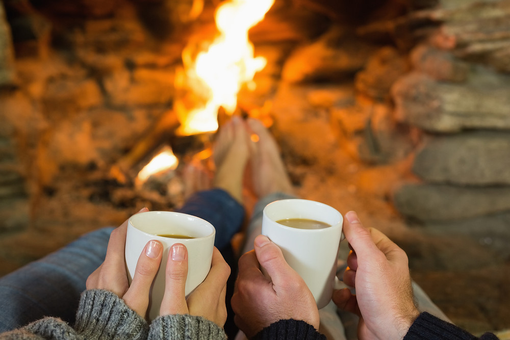 Close-up of hands holding coffee cups in front of lit fireplace.jpg