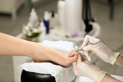 Woman receiving cuticle in manicure pedi