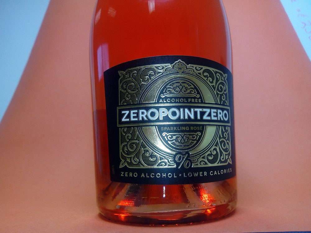 A foil label with Zero Point Zero and gold foil on a black background is on a clear bottle with ruby tinted contents