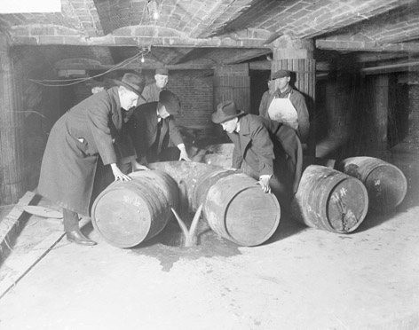 Six men in trench coats, in a creepy basement, sadly emptying alcohol barrels down a drain