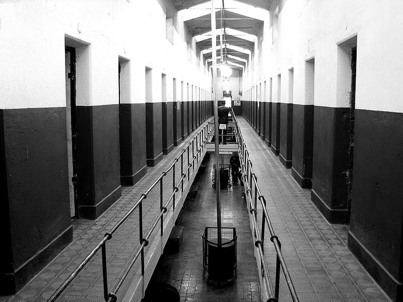 An empty multi level view along two balconies and down into a lower floow of a prison. Picture is start and austere