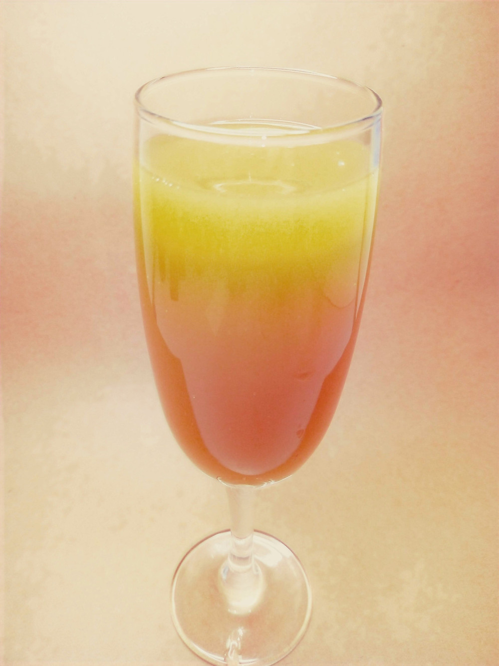 A glass is photographed slightly from above. The orange colour shades from light to dark down the shining curve of the glass.