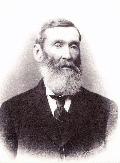 A black and white picture of an older middle aged white man with an impressive beard and high cheekbones
