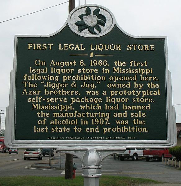 Picture of a sign in Mississippi. It states 'First Legal Liquor Store: On August 6th, 1966, the first legal liquor store in Mississippi following prohibition opened here. The 'Jigger & Jug' owned by the Azar brothers, was a prototypical self-serve package liquor store. Mississippi, which had banned the manufacturing and sale of alcohol in 1907, was the last state to end Prohibition.'