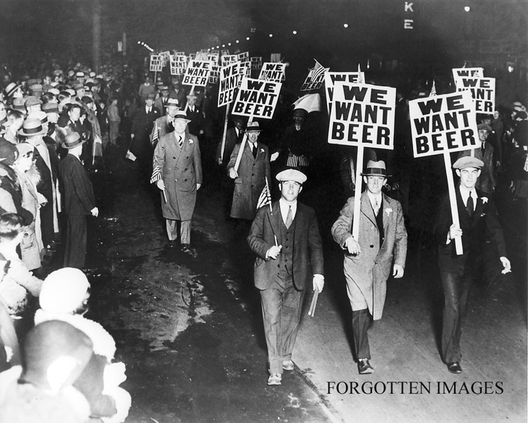 A night time rally with mainly men, the men marching are holding signs saying 'WE WANT BEER'