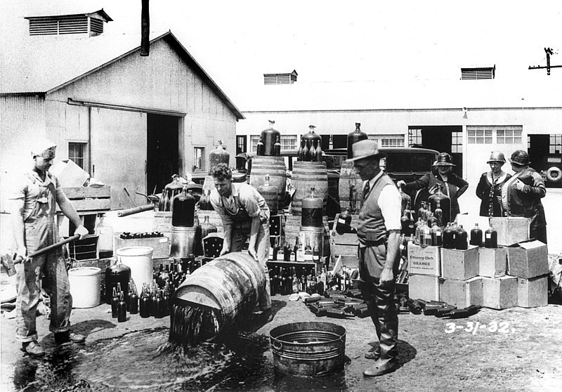 Three men and a woman looking at a barrel stoved in and being emptied of dark hued alcohol. The man holding the sledgehammer looks glum