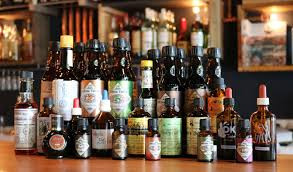 Picture of many different types of bitters bottles, showcasing the range of bottle types, shapes, labels ets. They are located on a bar with spirits bottles in the background.