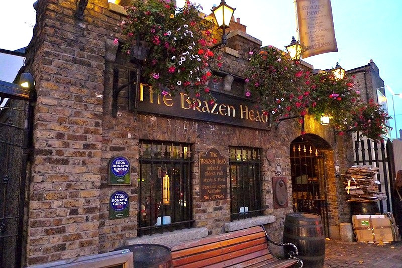 Picture of the sign 'The Brazen Head' attached to the front wall of the pub. The building is festooned with hanging flower baskets
