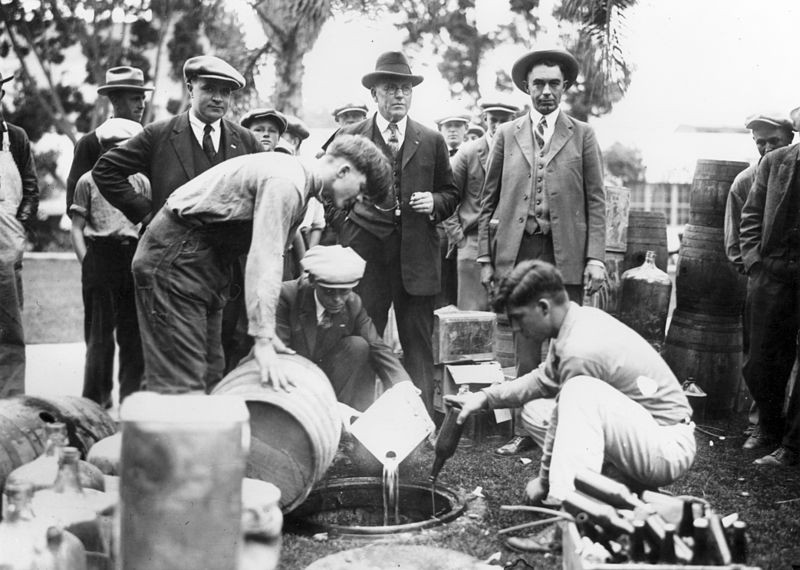 Three exasperated looking men in suits watching alcohol being poured down a drain.