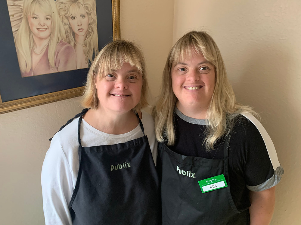 Two women with blonde hair standing in front of a pencil drawing of themselves hanging on the wall. The women are wearing work smocks identifying them as Publix employees.