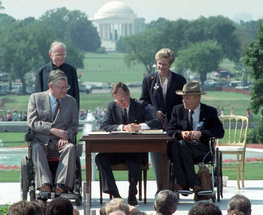 Justin Dart, Jr. with President George H.W. Bush signing the Americans with Disabilities Act in 1990.