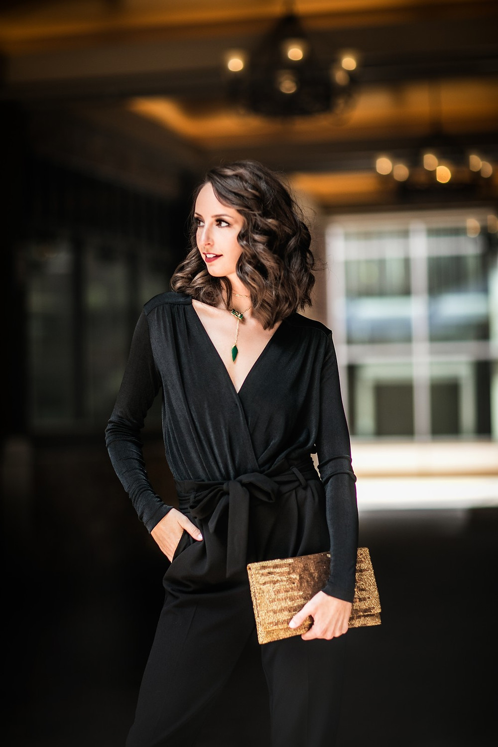 Fashion model in black jumpsuit with gold bag. Leawood Lifestyle Magazone.