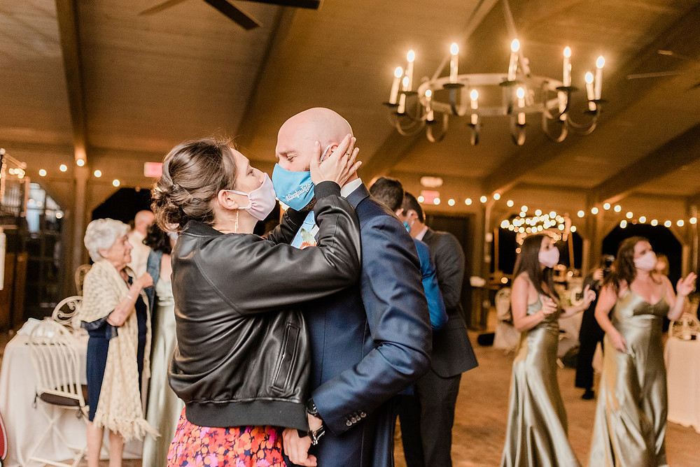 Two wedding guests kissing with masks on