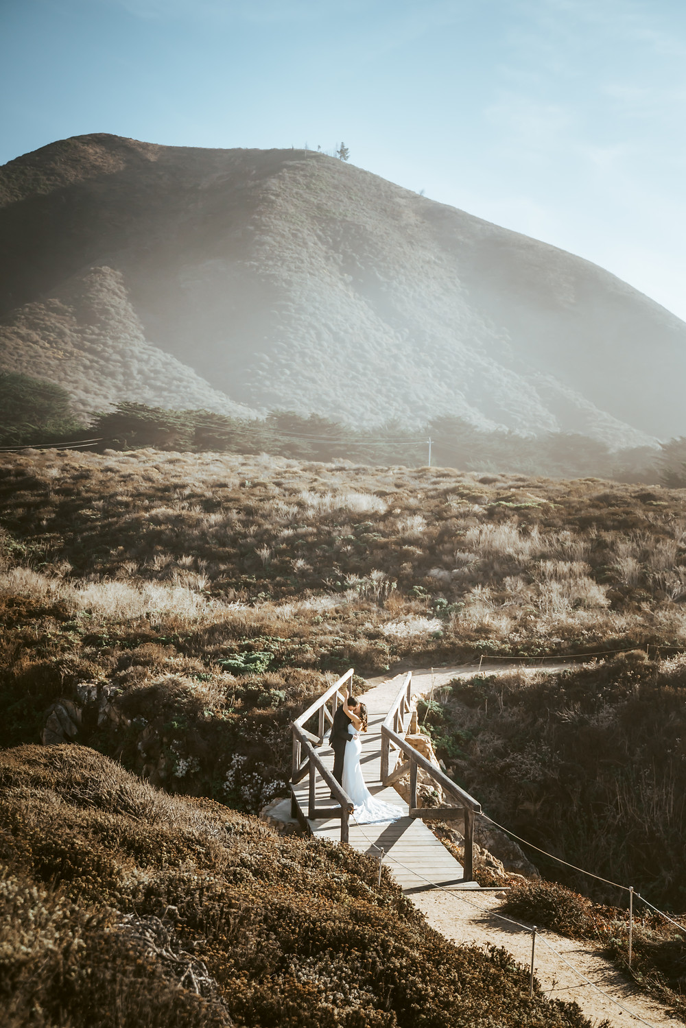 A bride kissing and standing on a bridge overlooking the mountains next to Big Sur