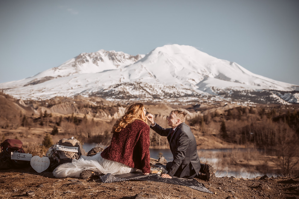 A bride and groom having a picnic in front of Mt. St. Helen's  with their hiking packs on the ground