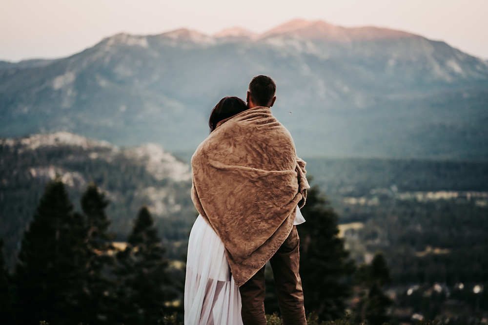 Bride and Groom wrapped in a blanket overlooking the mountain backdrop next to Lake Tahoe.  Photo is of eloping in Lake Tahoe