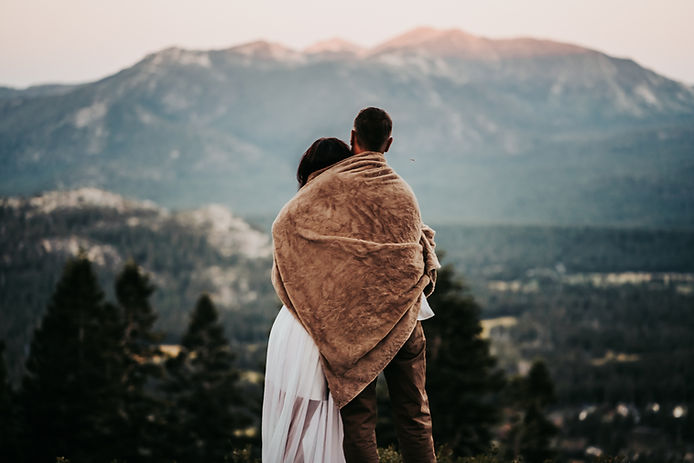 A couple wrapped in a blanket enjoying the sunset view of the mountains of Lake Tahoe after their adventure elopement